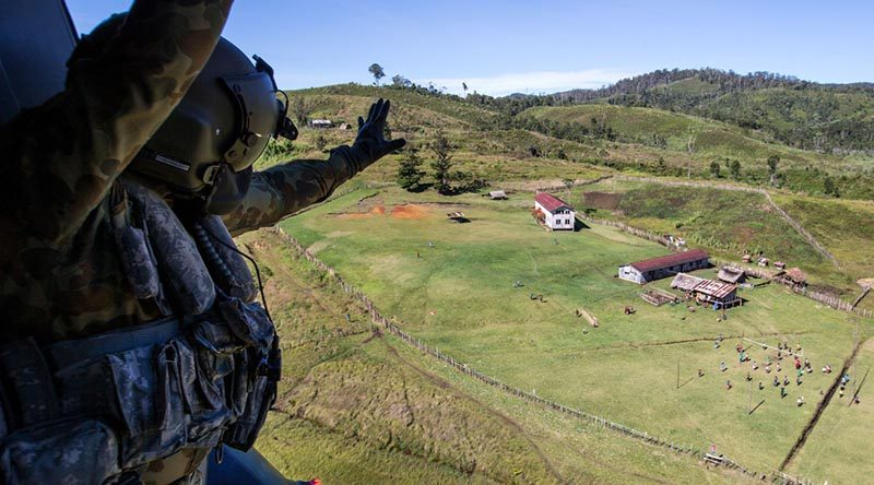 Australian Army soldier Corporal Rob Johnson, from the 5th Aviation Regiment in Townsville, waves to locals after conducting a community-engagement task during Operation Hannah in Papua New Guinea. Photo by Corporal Jake Sims.