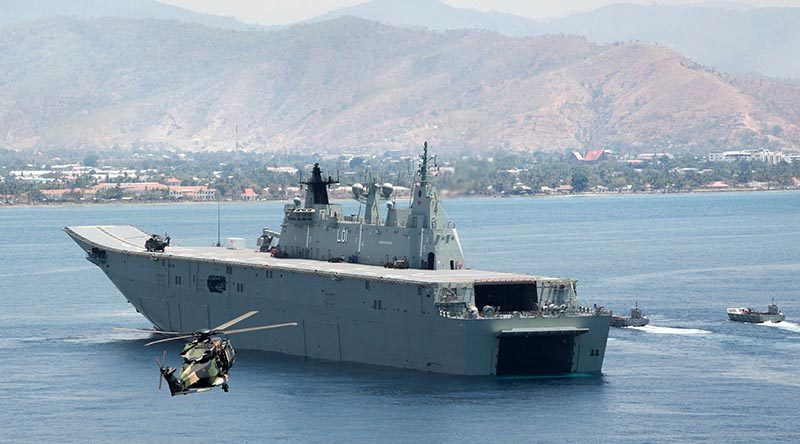 A MRH-90 Taipan helicopter delivers visitors from the Timor Leste government to HMAS Adelaide in Dili Harbour, as Navy and Army landing craft deliver a mobile hospital.