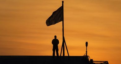 Signaller Aiden Barker prepares to lower the Australian National Flag at sunset on the Flight Deck of HMAS Adelaide while alongside Fort Hill Wharf, Darwin during Indo-Pacific Endeavour 17. Photo by Petty Officer Andrew Dakin.