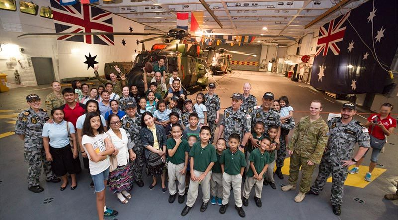 Crew from HMAS Adelaide pose with children and staff from the Amazing Grace Refuge Home, in Dinalupihan, Philippines during a visit to HMAS Adelaide while alongside in Subic Bay. Photo by Leading Seaman Peter Thompson.