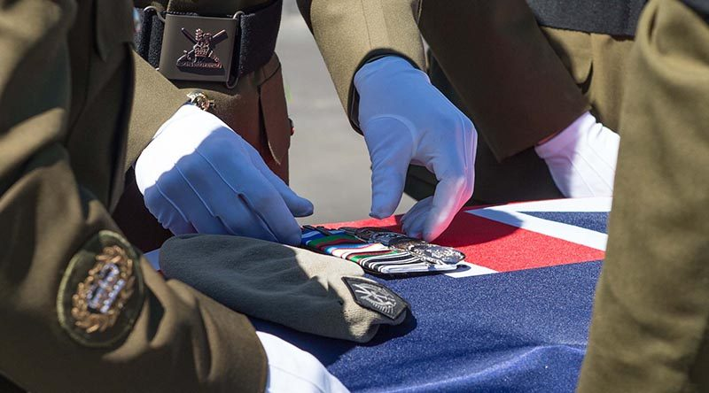Colleagues of Sergeant Wayne Taylor place his beret and medals on his casket during a private service at Papakura Military Camp, Auckland, New Zealand. NZDF photo.