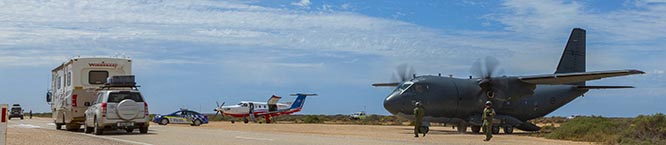 Traffic passes a C-27J Spartan from No 35 Squadron and a Royal Flying Doctors Service Pilatus PC-12, at the Chadwick Roadstrip – one of two designated emergency road landing strips along the Eyre Highway, Nullabor Plains, South Australia. Photo by Corporal David Gibbs.