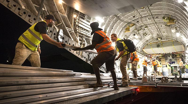 RAAF personnel are assisted by Department of Foreign Affairs and Trade, Palladium workers and Vanuatu locals to unload Australian Aid supplies from a C-17 Globemaster at Santo-Pekoa International Airport in Vanuatu as part of Operation Vanuatu Assist 2017. Photo by Leading Seaman Jake Badior.