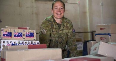 Task Group Taji postie Australian Army soldier Corporal Cassandra Rice is surrounded by work in the mail room at the Taji Military Complex, Iraq. Photo by Able Seaman Chris Beerens.