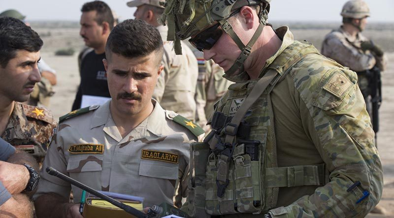 Australian Army officer Captain Nicholas Waugh confirms range and target coordinates with an Iraqi Army officer during a Forward Air Controller course live-fire component at Besmayah Range, Iraq. Photo by Corporal Chris Beerens.