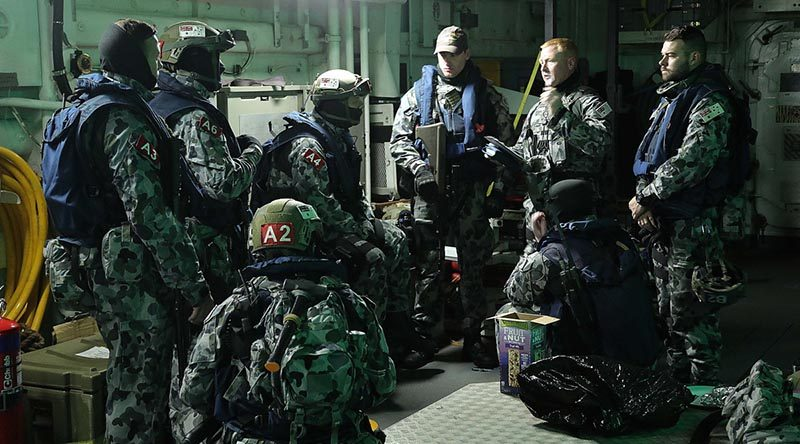 Chief Petty Officer Thomas Whitworth briefs HMAS Melbourne's boarding party during a tri-lateral exercise with United States and Republic of Korean Navies off the Korean coast. Photo by Able Seaman richard Cordell.
