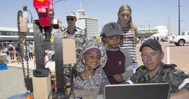 Petty Officer Chris White shows Akosua and Kk an auto targeting Nerf gun created for a robotics competition at the HMAS Stirling Fleet Support Unit-West display, during the Port of Fremantle Maritime Day held on Victoria Quay in Fremantle. Leading Seaman Bradley Darrell.