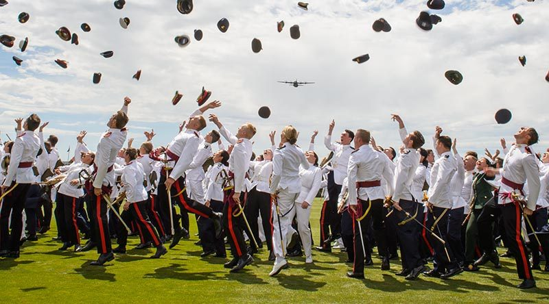 ADFA's graduating class of 2017 throw their hats in the air to symbolise completion of three years military training and academic studies as a C-130J Hercules flies over in salute. Photo by AHC Studios.
