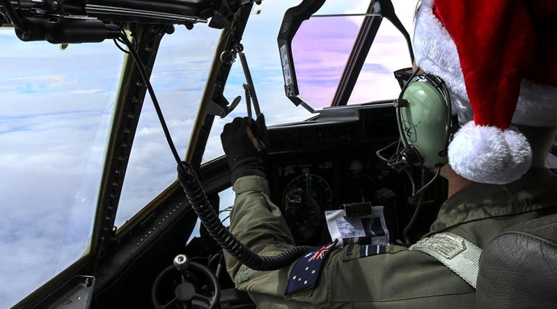 Royal Australian Air Force Flight Lieutenant Omar Rigo, 37 Squadron pilot, flies a Royal Australian Air Force C-130J Hercules toward Micronesian islands during Operation Christmas Drop. US Air Force photo by Staff Sergeant David Owsianka.