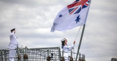 Able Seaman Samuel Millar and Able Seaman Alice Saunders lower HMAS Darwin's Australian White Ensign for the last time. Photo by Leading Seaman Kayla Hayes.