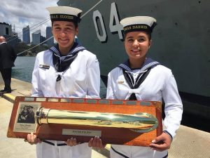 HMAS Success' Seaman Morgan Wilson-Ward, receives the First Lady of the Fleet honour board from HMAS Darwin's youngest female sailor, Seaman Letitia Jarvis-Soars.