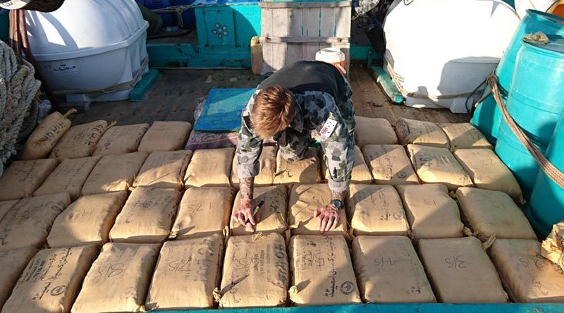 Leading Seaman Clearance Diver Luke Woodcroft from HMAS Warramunga numbers parcels of seized narcotics on the deck of a trafficking vessel. Photo by Leading Seaman Tom Gibson.