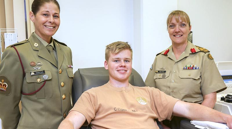 Army Blood Ambassador, Warrant Officer Class Two Geneen Lord and Brigadier Leigh Wilton provide encouragement to Officer Cadet Don Considine as he donates plasma during the Defence Blood Challenge, in Canberra on 1 September 2017. Photo by Corporal Bill Solomou.