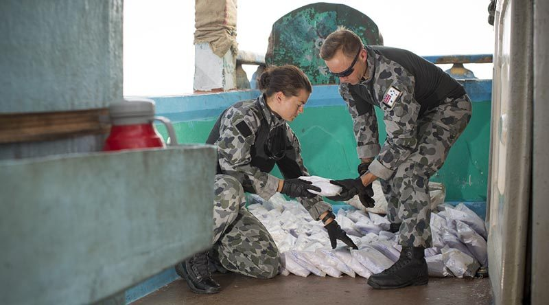 Able Seaman Stephanie Pannell passes a bag a seized narcotics to Leading Seaman James Walker during an illicit cargo seizure by HMAS Warramunga in the Middle East. Photo by Leading Seaman Tom Gibson.