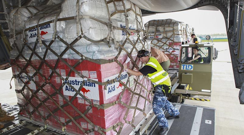 RAAF Amberley air-load team members load pallets of Australian Aid onto a RAAF C-17A Globemaster for delivery to Tonga. Photo by Sergeant Peter Borys.