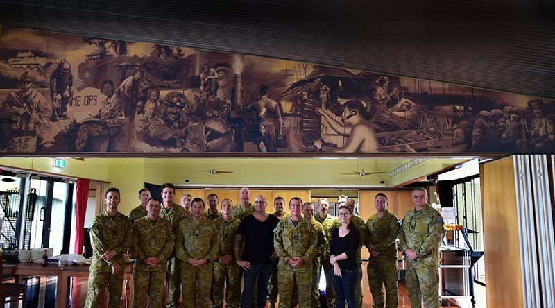 Artists Rob Douma and KellyBianchi pose beneath their muralwith Chauvel Sergeants' Mess PMC WO1 Brent Doyle and other members of the Mess Committee.