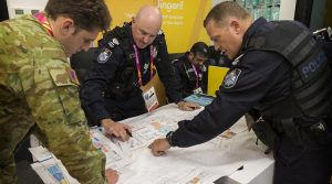 Queensland Police Service officers, Acting Senior Sergeant Mike Cahill (right) and Sergeant Brendon Carr discusses security plans with Australian Army officer Captain Maddison Cullen during a search of the 2018 Commonwealth Games athlete's village. Photo by Sergeant W Guthrie.