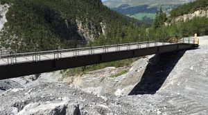 A dry support bridge deployed after severe flooding destroyed a road.