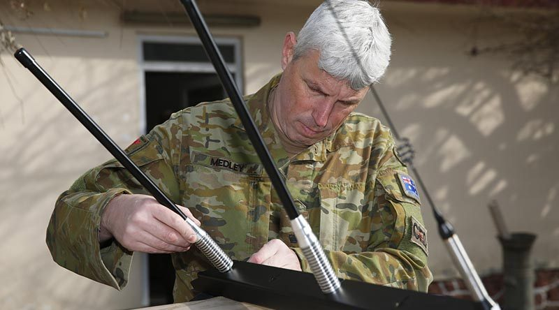 Australian Army officer Lieutenant Colonel Jason Medley prepares to install a Slivershield electronic force protection system, designed for the Afghan National Defence and Security Forces to counter radio-controlled improvised explosive devices. Photo by Sergeant Max Bree.