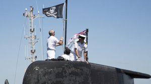 Executive Officer HMAS Dechaineux Lieutenant Commander Darren White raises the 'Jolly Roger' on Collins-class submarine HMAS Dechaineux at Fleet Base West. Official Defence photo by Chief Petty Officer Damian Pawlenko.
