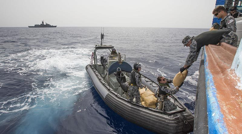 Leading Seaman James Walker (right) passes a parcel of seized narcotics to Able Seaman Stephanie Pannell during a drug-seizure operation in the Middle East. Photo by Leading Seaman Tom Gibson.