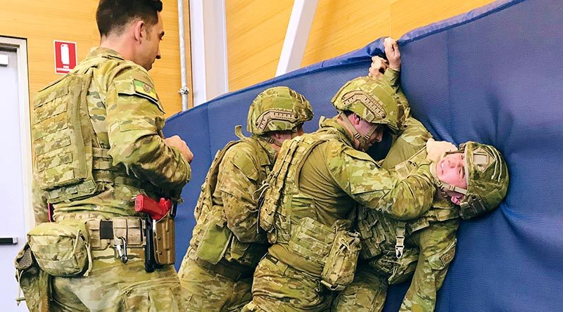 Under the watchful eye of an instructor, soldiers from the 1st Brigade practise subduing an enemy soldier during an Army Combatives Program training session at RAAF Edinburgh. 7RAR photo.