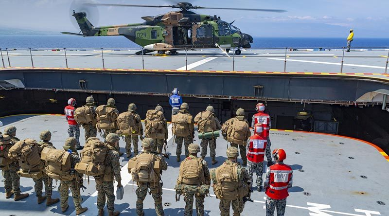 United States Marines prepare to board HMAS Adelaide's MRH-90 helicopter in support of amphibious operations off the coast of Hawaii, as part of Exercise RIMPAC 2018. Photo by Able Seaman Ronnie Baltoft.