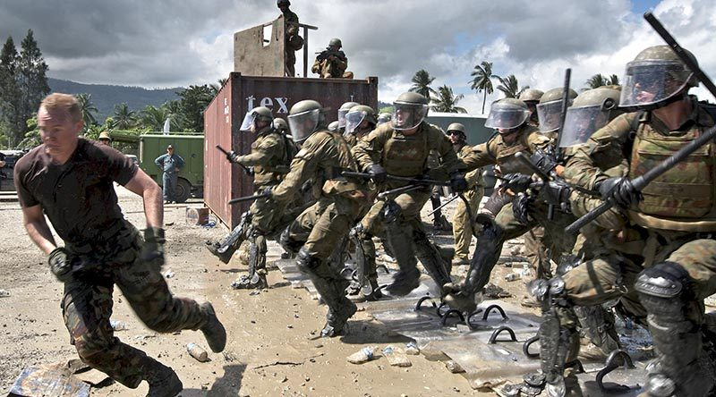 Australian soldiers break ranks and charge unruly (New Zealand soldier) protesters during a Population Protection and Control (PPC) training exercise. Photography by Leading Seaman Paul Berry.
