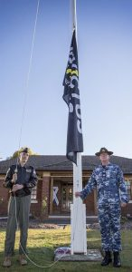 Commander Royal Australian Air Force Air Mobility Group Air Commodore William Kourelakos and Warrant Officer Ian Wheatley hoist the Invictus Games flag at RAAF Base Richmond. Photo by Corporal Casey Forster.