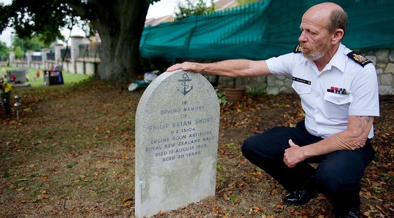 Warrant Officer Ken Bancroft who is leading the vigil team of Royal New Zealand Navy sailors in England, examines the headstone of Engine Room Artificer Apprentice Philip Short, 20, who was killed in a vehicle accident and buried in England in 1958. NZDF photo.