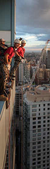 Able Seaman Madeline Whatley and Able Seaman Savannah Tansey prepare to abseil from a Sydney skyscraper.