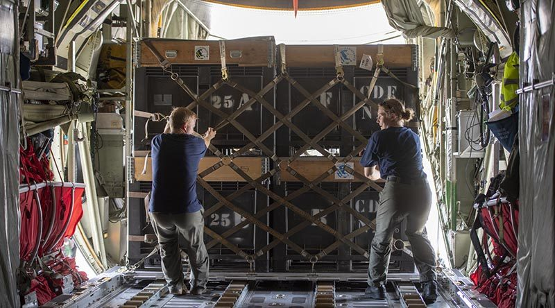 Air Warfare Officer Flight Lieutenant Adam Palmer and Air Loadmaster Corporal Toni Thompson load aid into a Royal New Zealand Air Force C-130 Hercules, for delivery Palu, at the 'air bridge' in Balikpapan airport. NZDF photo.