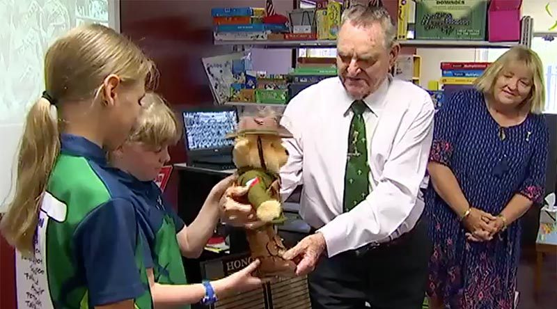 Keith Payne VC hands Trooper Bert Jones over to students at Dundula State School in Baker's Creek, Queensland, to use as a teaching aid and an Anzac reminder. Screen grab from Channel 7 news report.