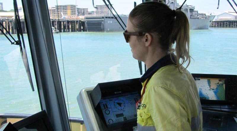 Darwin-based tugboat driver Alicia Pollock in Darwin Harbour (with Singapore's Endurance-class landing ship tank RSS Endeavour docked in the background). Serco photo.