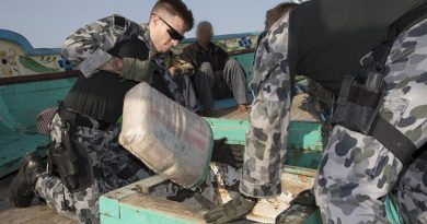 Leading Seaman Aaron Wheeler pulls a sack containing suspected illegal narcotics from the hold in a dhow. Photo by Leading Seaman Bradley Darvill.