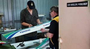 Leading Cadet Connor Bonham (608 Squadron, Gawler) receives guidance on repairing and cleaning a radio-controlled fixed-wing aircraft (a Kyoshu Calmato high wing trainer with a 60-size engine) from Sergeant (AAFC) Shayne O'Hara. Photo by Flying Officer (AAFC) Paul Rosenzweig