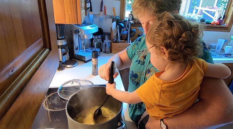 Zoe helps Nana stir Grandad's seafood chowder.
