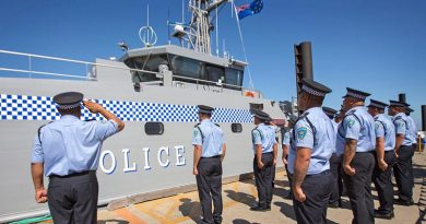 Members of the Tuvalu Police Force salute the rising of their national flag for the first time on their new Guardian-class patrol boat, gifted by Australia. Photo by Petty Officer James Whittle.