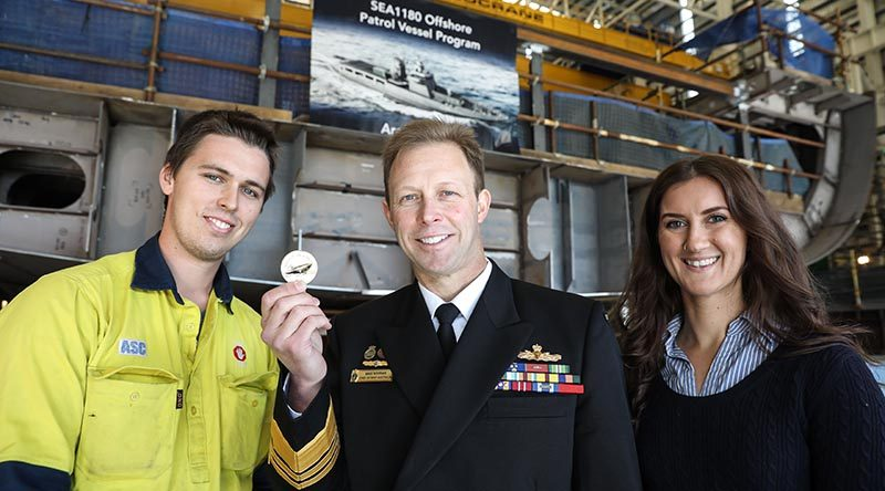 Boilermaker Kane Ramsay and Document Editor Lauren Pitman prepare to assist Chief of Navy Vice Admiral Michael Noonan to lay a traditional coin under the keel of the future HMAS Arafura. Photo supplied by ASC.