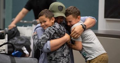 A New Zealand Defence Force soldier returning home after a six-month deployment in Iraq hugs his two sons upon arrival at Royal New Zealand Air Force Base Ohakea this afternoon. NZDF photo.