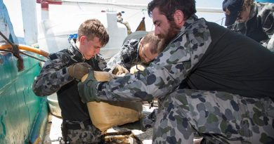 Able Seaman Justin Springer and Leading Seaman Daniel Colliver remove sacks containing suspected narcotics from a dhow's hold in the Middle East. Photo by Leading Seaman Bradley Darvill.