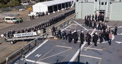 HMAS Newcastle's decommissioning crew march off their ship for the last time.
