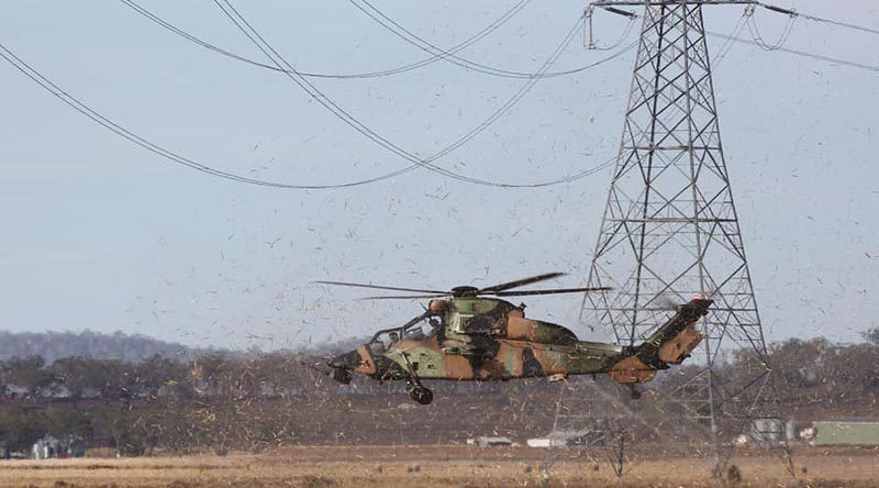 An ARH Tiger from the Army Aviation Training Centre at Oakey practices flying under-wires. The ability for the aircraft to use terrain masking greatly increases survivability against an enemy with advanced weaponry, increasing lethality and reconnaissance ability. Photo by Bradley Richardson.