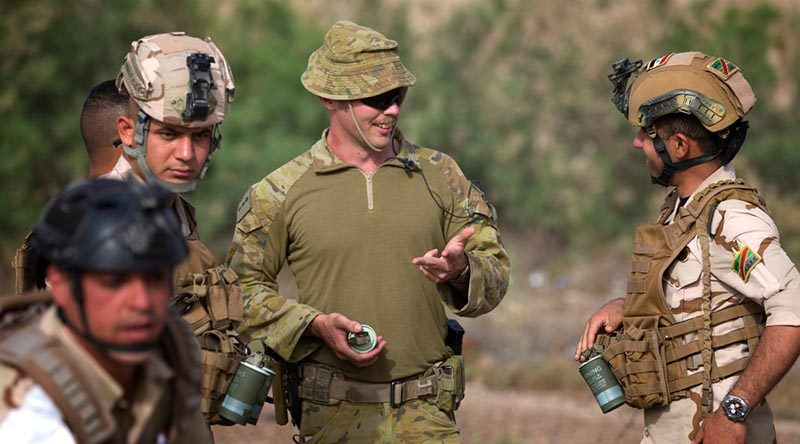 Australian Army officer Captain Jeremy Duff (centre), deployed with Task Group Taji 8, speaks with an Iraqi Army soldier before the Mission Rehearsal Exercises at the Taji Military Complex. Photo by Corporal Oliver Carter.