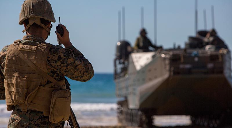 A US Marine speaks on a radio during the Combined Force Entry Operation during Exercise Talisman Sabre 19 during an amphibious landing at Stanage Bay, Queensland. US Marine Corps photo by Lance Corporal Kaleb Martin.