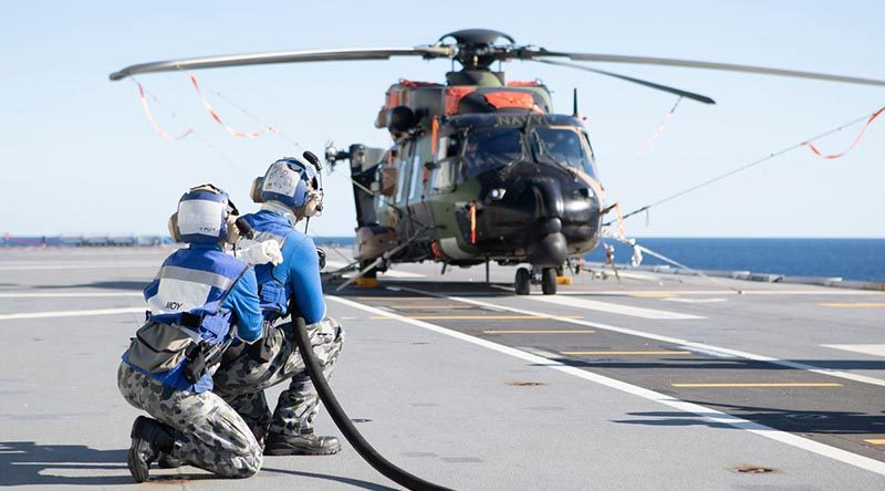 HMAS Canberra's flight deck team conduct crash-on-deck training with a grounded MRH-90 helicopter during Exercise Talisman Sabre 2019. Defence made no mention of the fleet-wide MRH90 grounding until asked by media nearly two weeks after this photo was published. Photo by Leading Seaman Richard Cordell.