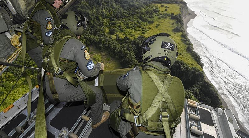 Corporal Toni Thompson, Sergeant Ethan Moran and Corporal Nicholas Morse, Royal New Zealand Air Force air loadmasters with No.40 Squadron, watch a parachute load fall to its target on Raoul Island off the their C-130H(NZ) Hercules. RNZDF photo.