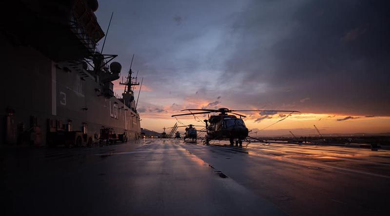 HMAS Adelaide and her embarked helicopters bask in a Solomon Islands sunset.
