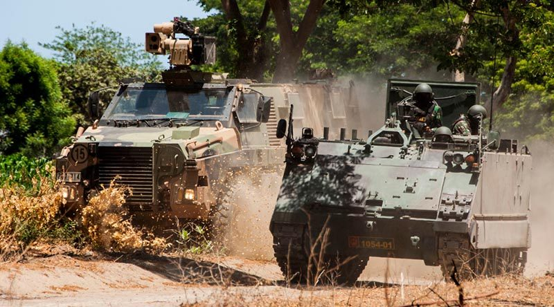 An Australian Army Bushmaster conducts tactical mounted manoeuvres with an M113/AS1 from the Tentara Nasional Indonesia Army (TNI-AD) at Dodiklatpur training base, East Java. Photo by Corporal Shane Kelly.