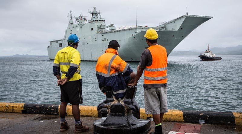 Port of Suva workers watch as Canberra-class Landing Helicopter Dock HMAS Adelaide (III) prepares to come alongside at Kings Wharf in Suva, Fiji. Photo by Corporal Jessica de Rouw.